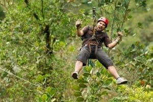 Man zip lining through the woods